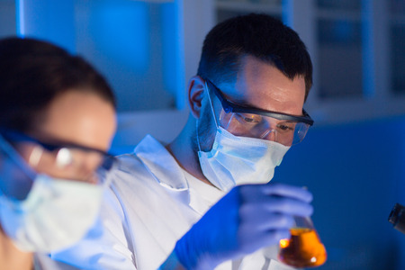 BIOLOGIA: la ciencia, la química, la biología, la medicina y el concepto de la gente - cerca de los jóvenes científicos con pipetas y frascos que hacen prueba o investigación en laboratorio clínico