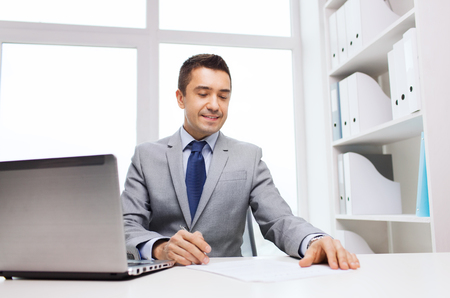smiling businessman: business, people, paperwork and technology concept - smiling businessman with laptop computer and papers working in office
