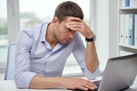 ansiedad: negocio, gente, fecha límite y la tecnología concepto - hombre de negocios tensionado con el ordenador portátil en la oficina