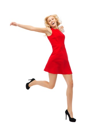 women legs: people, emotion, expression, happiness and holidays concept - happy young woman in red dress jumping high in air