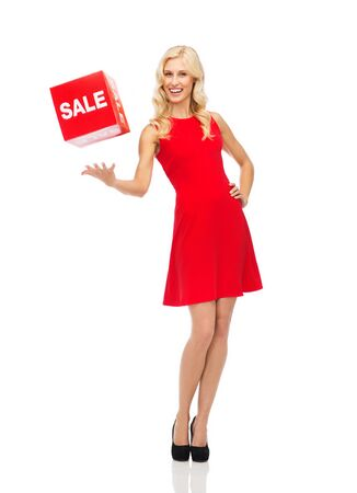 sale sign: people, shopping, discount and holidays concept - smiling woman in red dress holding cardboard box with sale sign