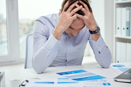 stress: business, people, paperwork and deadline concept - stressed businessman with papers and charts sitting at table in office