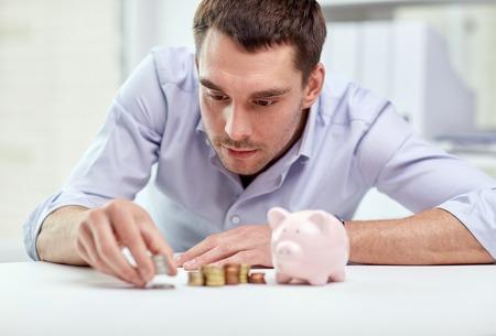 argent: affaires, des gens, des finances et de l'argent notion d'économie - homme d'affaires avec tirelire et pièces de monnaie au bureau