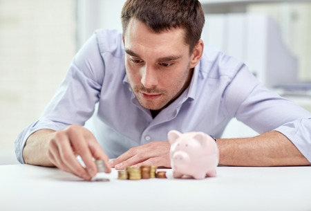 investing: business, people, finances and money saving concept - businessman with piggy bank and coins at office