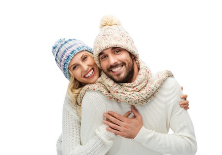 ropa de invierno: invierno, la moda, de pareja, de la navidad y la gente concepto - hombre sonriente y la mujer en los sombreros y abrazos bufanda