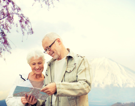 guide: family, age, tourism, travel and people concept - senior couple with map and city guide over japan mountains background