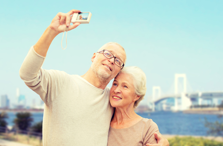 couple outdoor: age, tourism, travel, technology and people concept - senior couple with camera taking selfie on city street over rainbow bridge in tokyo and river background Stock Photo