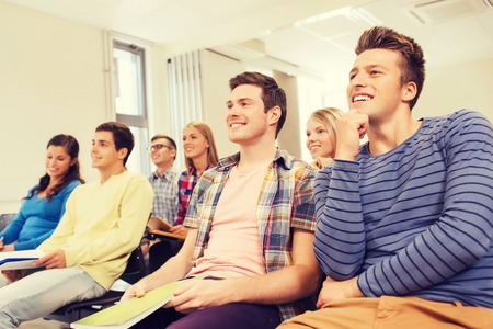 lecture: education, high school, teamwork and people concept - group of smiling students with notepads sitting in lecture hall Stock Photo
