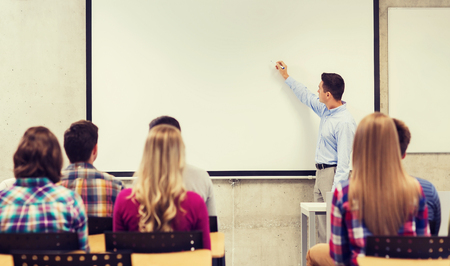 students: education, high school, teamwork and people concept - smiling teacher standing in front of students and writing something on white board in classroom Stock Photo
