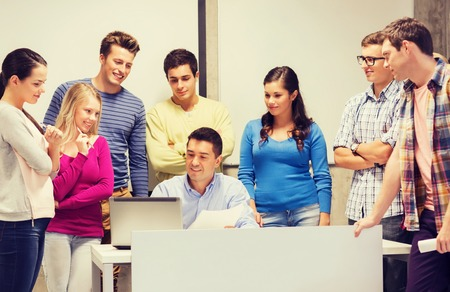 computer class: education, high school, technology and people concept - group of smiling students and teacher with papers, laptop computer in classroom