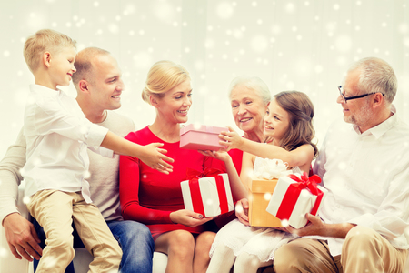 three presents: family, holidays, generation, christmas and people concept - smiling family giving each other presents  at home Stock Photo