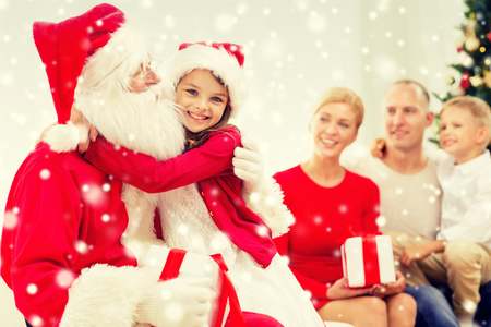 family, holidays, generation, christmas and people concept - smiling family with santa claus and gift boxes at home Stock Photo