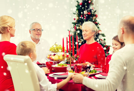 familia orando: familiares, vacaciones, generación, Navidad y la gente concepto - sonriendo familia cenando y orando en casa Foto de archivo