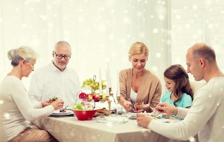 家庭: 家庭,度假,發電,聖誕節和人的概念 - 微笑以在家用餐的家庭