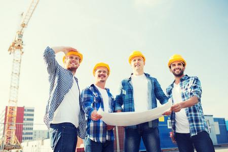 negocio, construcción, trabajo en equipo y concepto de la gente - grupo de sonrientes constructores de cascos con el modelo al aire libre