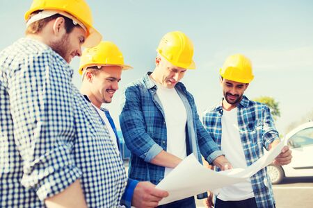 construction site: business, building, teamwork and people concept - group of smiling builders in hardhats with blueprint outdoors Stock Photo