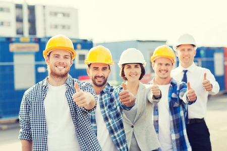 zaken, gebouw, teamwerk, gebaar en mensenconcept - groep glimlachende bouwers in bouwvakkers die duimen in openlucht tonen