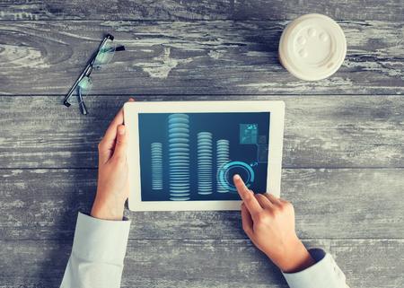cuenta bancaria: negocios, personas, finanzas y tecnología concepto - cerca de las manos apuntando el dedo a la pantalla del ordenador Tablet PC con bitcoin, taza de café y gafas en la mesa Foto de archivo