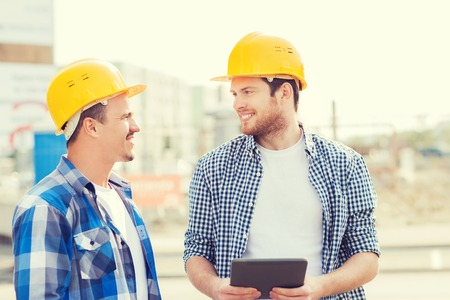 construction workers: business, building, teamwork, technology and people concept - group of smiling builders in hardhats with tablet pc computer outdoors Stock Photo