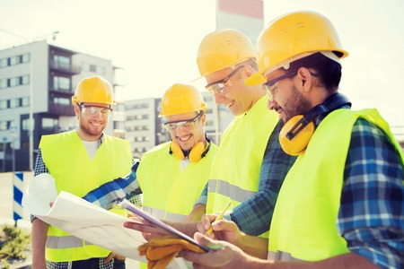 construcci�n: negocio, construcci�n, trabajo en equipo y concepto de la gente - grupo de sonrientes constructores de cascos con el portapapeles y modelo al aire libre Foto de archivo