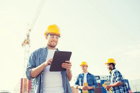 business, building, teamwork, technology and people concept - group of smiling builders in hardhats with tablet pc computer outdoors Archivio Fotografico