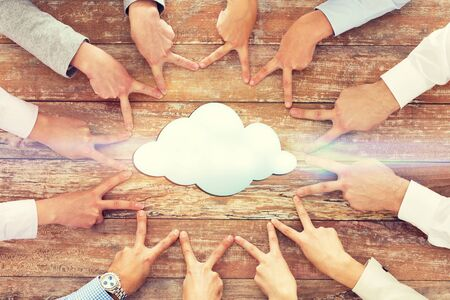 gestures: business, people, gesture and team work concept - close up of creative team showing victory hand sign on table with cloud icon Stock Photo