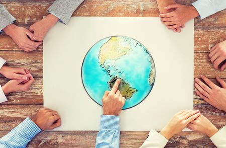 planet earth: global business, people and team work concept - close up of hands on table pointing finger to earth globe picture in office