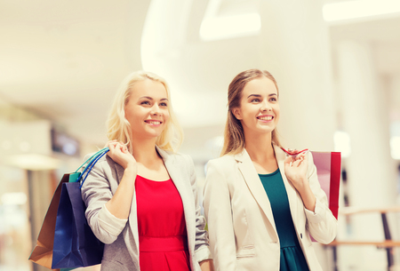 consumerism: sale, consumerism and people concept - happy young women with shopping bags in mall Stock Photo