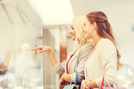 woman bag: sale, consumerism and people concept - happy young women with shopping bags pointing finger in mall