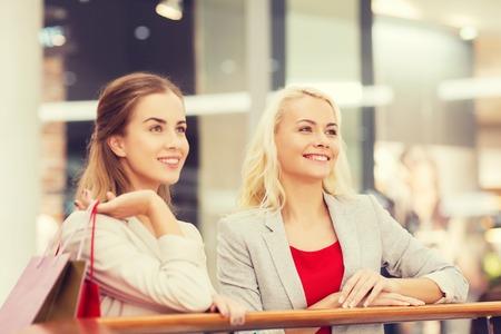 mujeres felices: venta, el consumismo y el concepto de la gente - las mujeres jóvenes felices con bolsas de compras en centro comercial