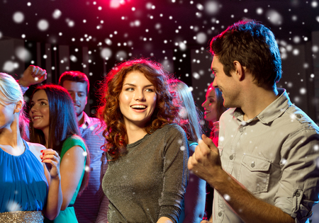 christmas party: party, holidays, celebration, nightlife and people concept - smiling friends dancing in club