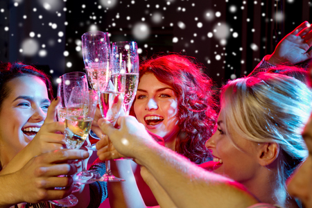 holiday music: party, holidays, celebration, nightlife and people concept - smiling friends with glasses of non-alcoholic champagne in club