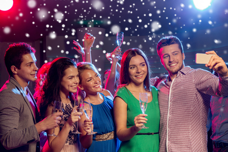 young people party: party, holidays, technology, nightlife and people concept - smiling friends with glasses of non-alcoholic champagne and smartphone taking selfie in club