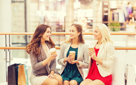 women coffee: sale, consumerism and people concept - happy young women with shopping bags and coffee paper cups in mall Stock Photo