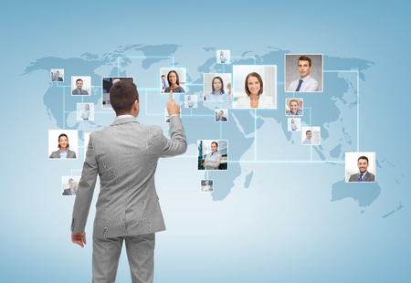 business, people, communication and technology concept - businessman pointing finger to contact icons on world map over blue background from back