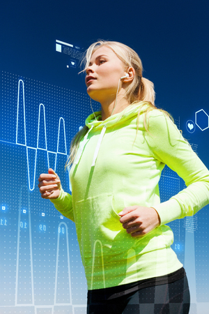 heart monitor: sport, fitness, exercise and lifestyle concept - woman doing running with earphones outdoors Stock Photo