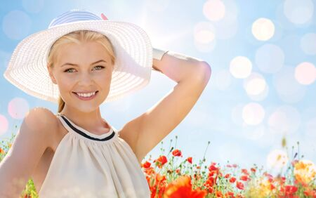 woman smiling: happiness, nature, summer, vacation and people concept - smiling young woman with closed eyes wearing straw hat on poppy field
