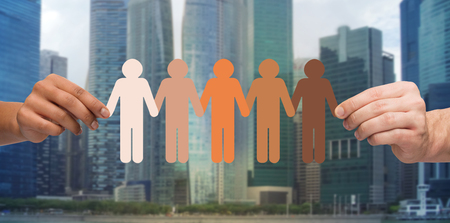 community people: community, unity, population, race and humanity concept - multiracial couple hands holding chain of paper people pictogram over singapore city background