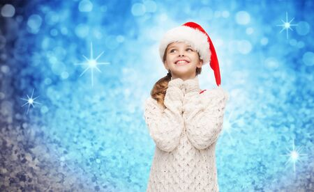 girl looking up: christmas, winter, holidays and childhood concept - dreaming girl in santa helper hat over blue glitter or lights background Stock Photo
