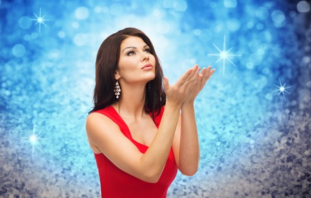 red and blue: people, holidays, christmas, magic and fashion concept - beautiful sexy woman in red dress blowing fairy dust off over blue glitter or lights background Stock Photo