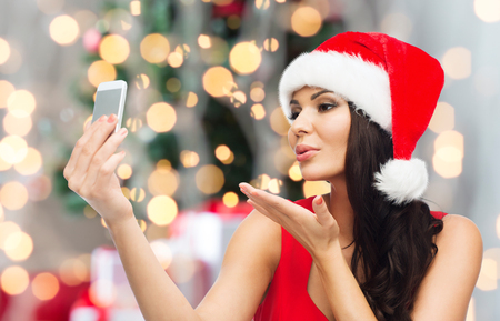 hot chick: people, holidays, christmas and technology concept - beautiful sexy woman in red santa hat taking selfie picture by smartphone and sending blow kiss to camera over lights background