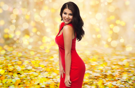 people, holidays and fashion concept - beautiful sexy woman in red dress over yellow lights or golden confetti background