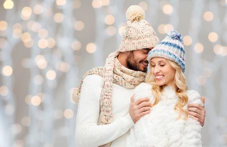 fashion: hiver, la mode, couple, noël et les gens notion - en souriant homme et la femme dans les chapeaux et foulard étreindre pendant les vacances de lumières fond
