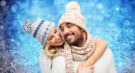 sonrisa: invierno, la moda, de pareja, de la navidad y la gente concepto - hombre sonriente y la mujer en sombreros y abrazos bufanda sobre fiestas luces azules o fondo del brillo