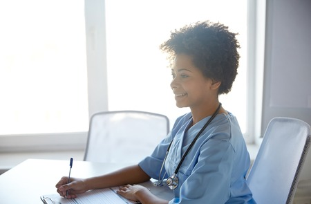 black nurse: health care, profession, people and medicine concept - happy female doctor or nurse with clipboard and pen writing at hospital