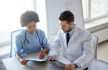health care, people, technology and medicine concept - doctor and nurse with tablet pc computer and clipboard meeting and discussing something at hospital Stock Photo