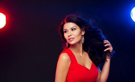 latin dance: people, holidays, disco, night lifestyle and leisure concept - beautiful sexy woman in red dress at nightclub Stock Photo