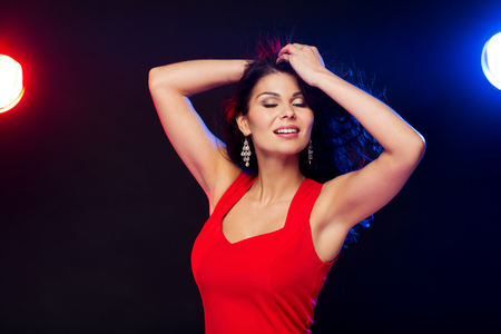 donna che balla: persone, vacanze, discoteca, lo stile di vita di notte e concetto di tempo libero - bella donna sexy in abito rosso ballare in discoteca Archivio Fotografico
