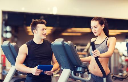 健身: 運動,健身,生活方式,技術和人的概念 - 女人與教練對運動步進在健身房