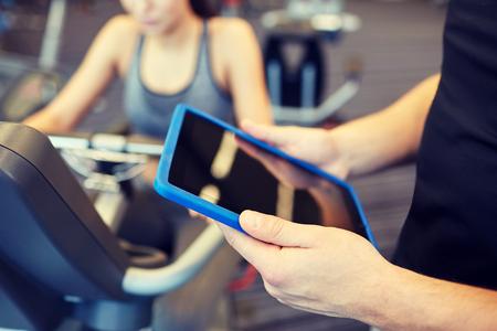Sport, Fitness, Lifestyle, Technik und Menschen-Konzept - Nahaufnahme von Trainer H�nde mit Tablette-PC-Computer und Frau, die auf Heimtrainer im Fitness-Studio